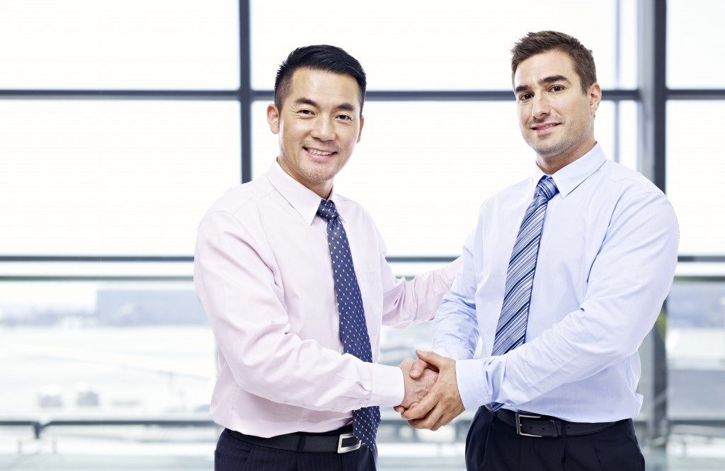 Asian expat shaking colleague's hand