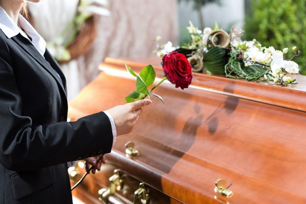 Woman holding a red rose beside the casket