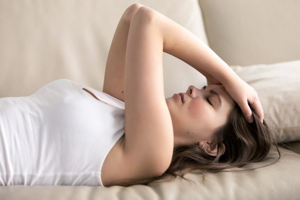 fatigued woman lying on couch