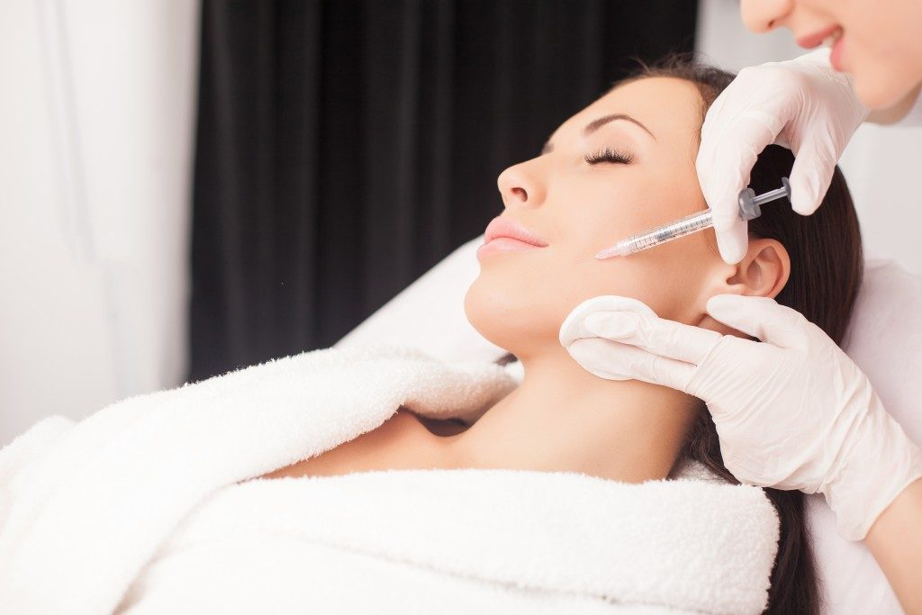 Cosmetologist injecting botox