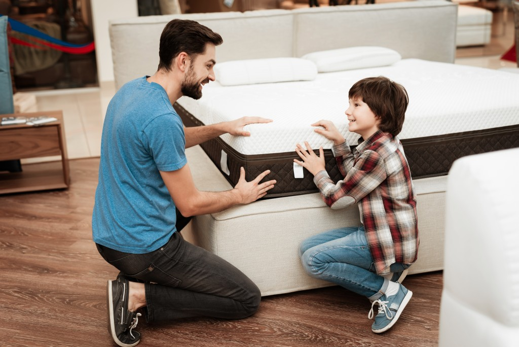 dad and son shopping for mattress