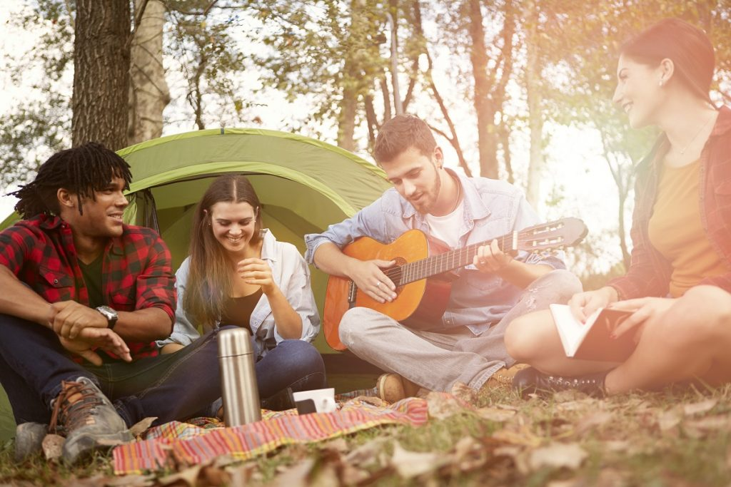 people on a camping playing the guitar