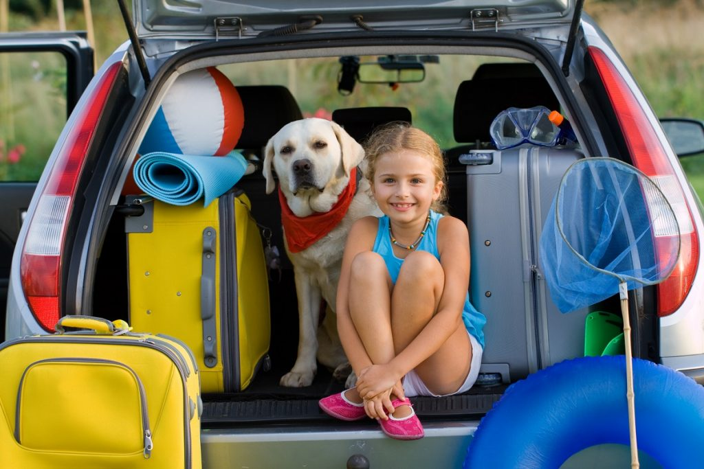 young girl at the back of car with her dog