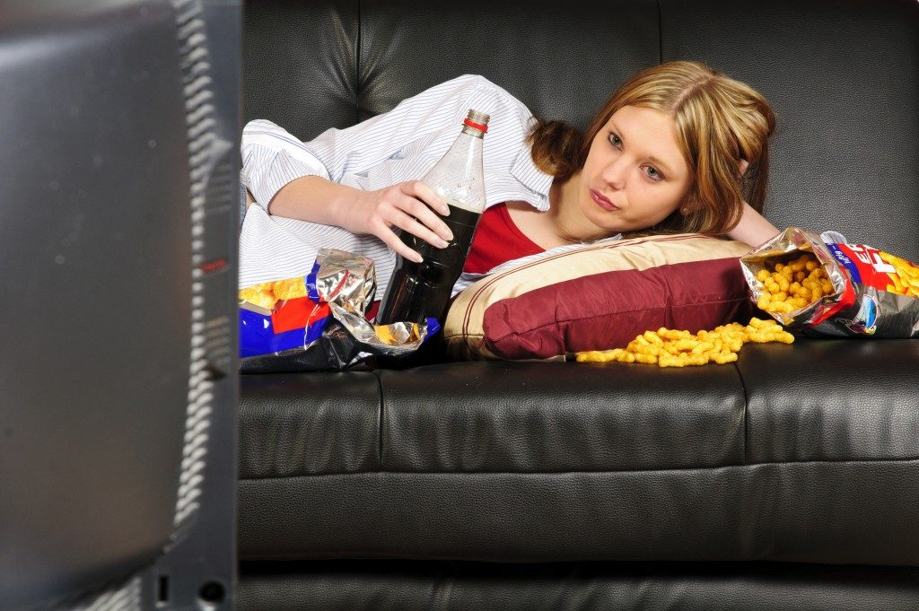 woman laying on the couch while eatinf junk foods and drinking softdrinks