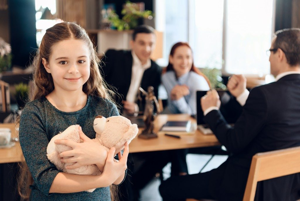 little girl holding a teddy bear with her parents and a lawyer at the back