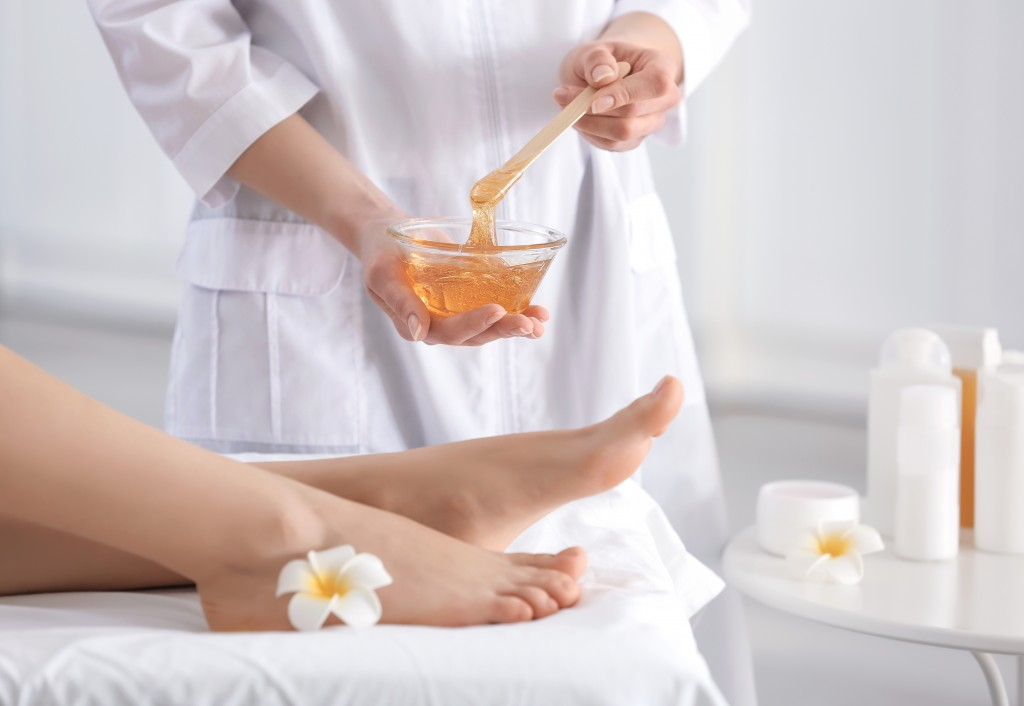 waxing salon with woman holding hot wax