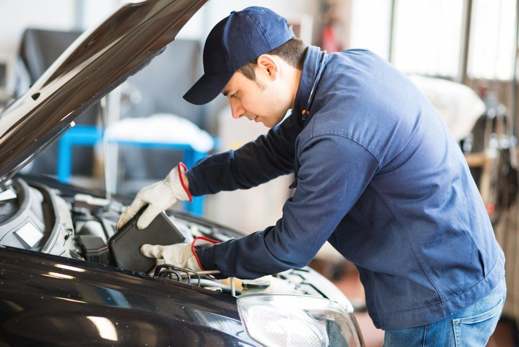 Auto mechanic putting oil