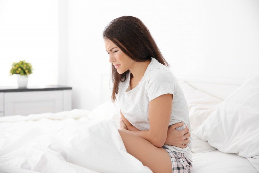 Young woman with stomach ache sitting on bed