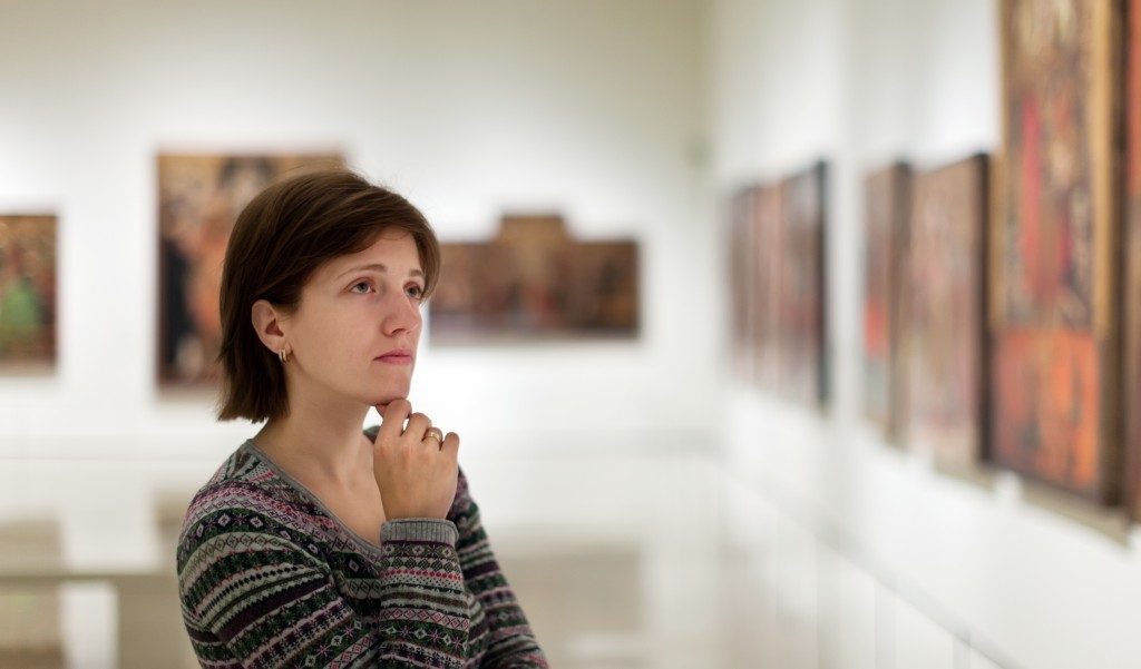 visitor looking pictures in art gallery