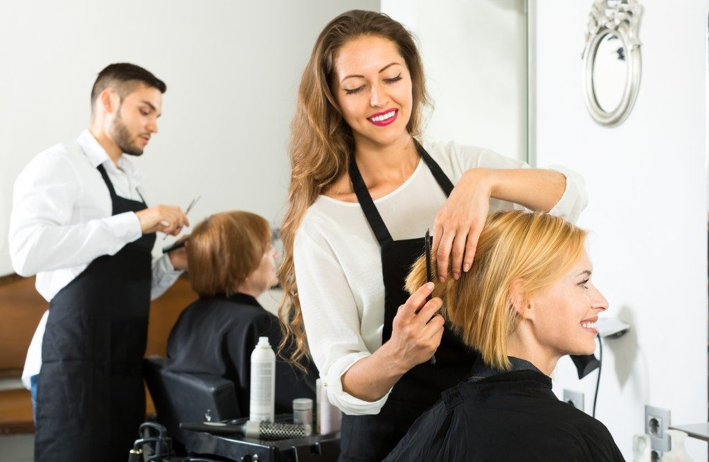 Smiling client sitting in a hair salon while hairdresser is combing her hair