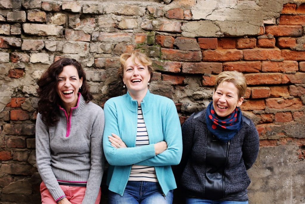 Three women laughing and leaning on the brick wall