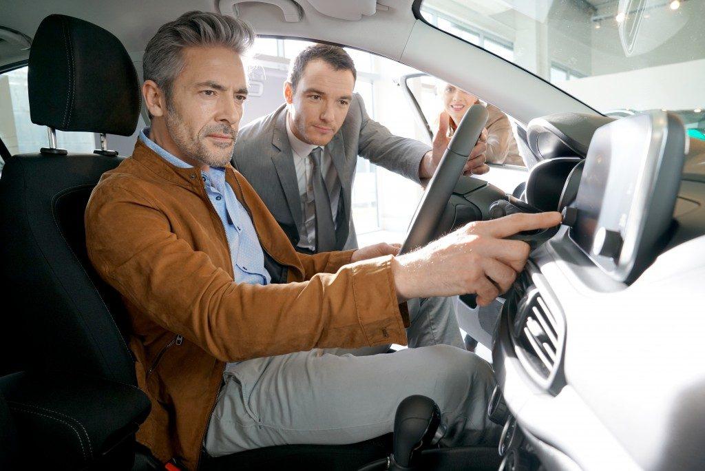 car salesman assisting a customer
