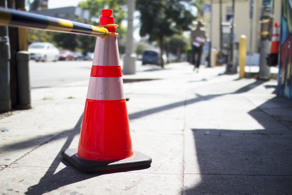 orange hazard cone on pavement