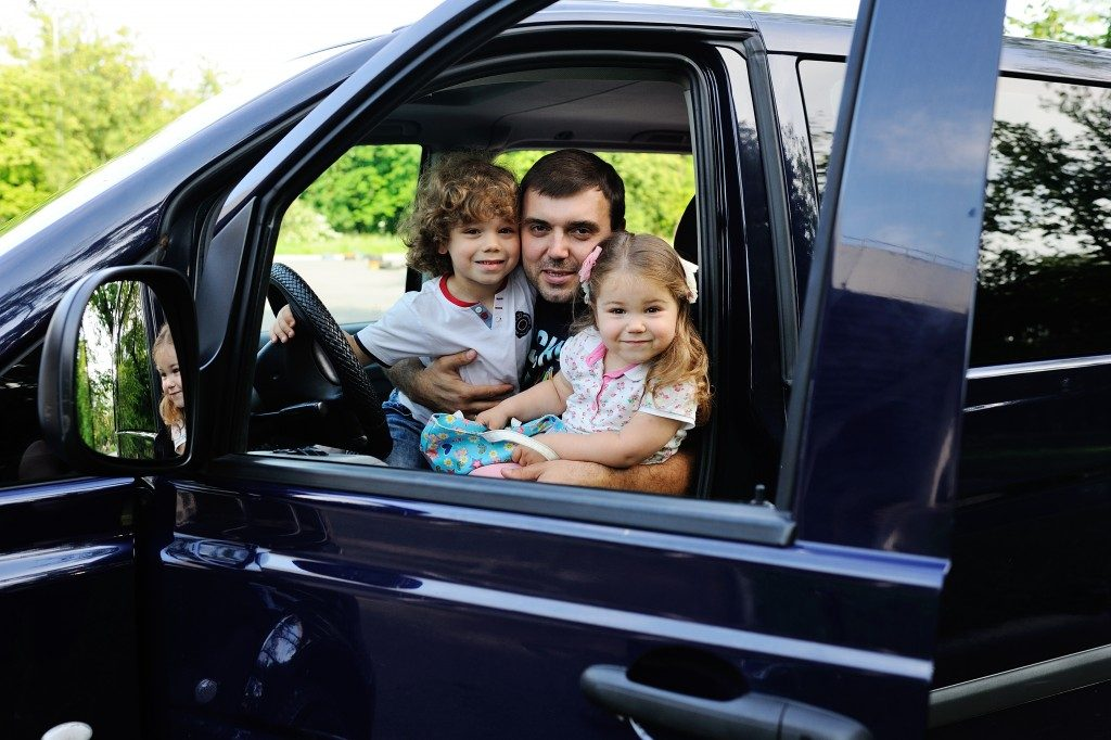 dad and kids at the front seat of a parked van