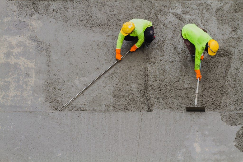 workers flatenning the concrete floor