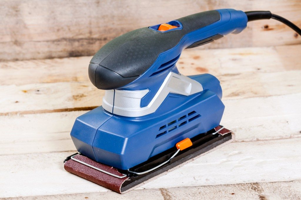 Electrical sander tool on wooden background