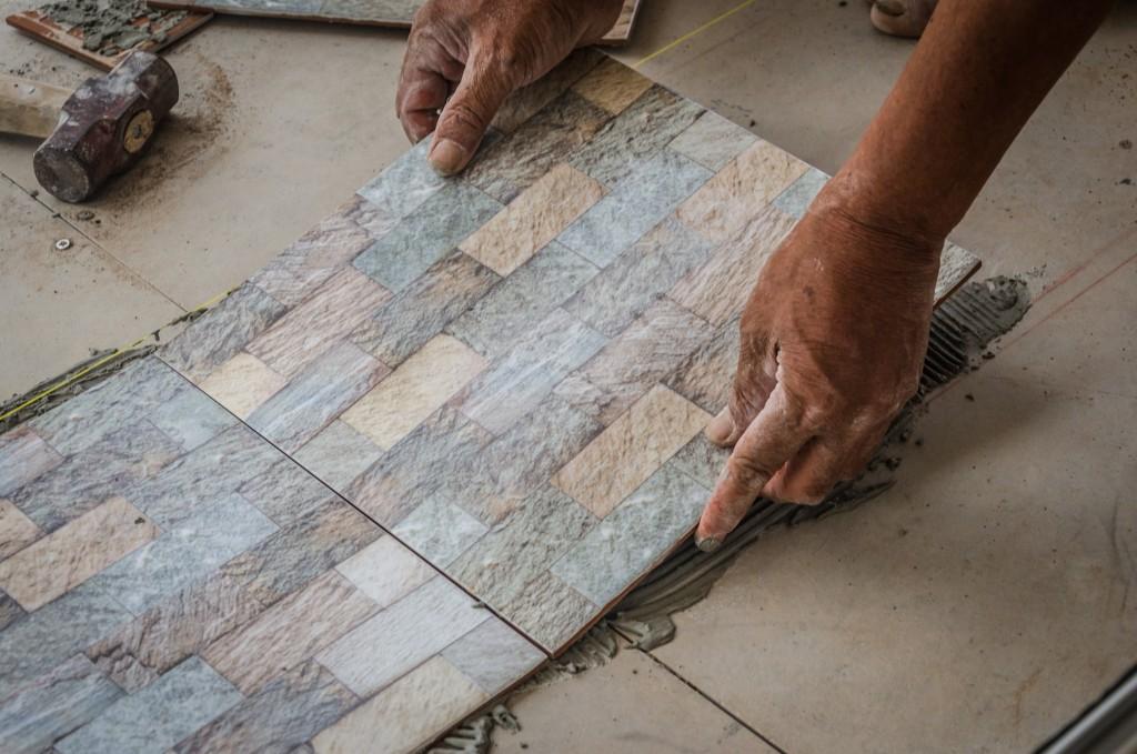 person installing floor tiles