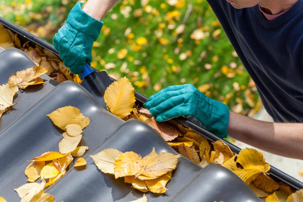 Man cleaning gutter full of leaves
