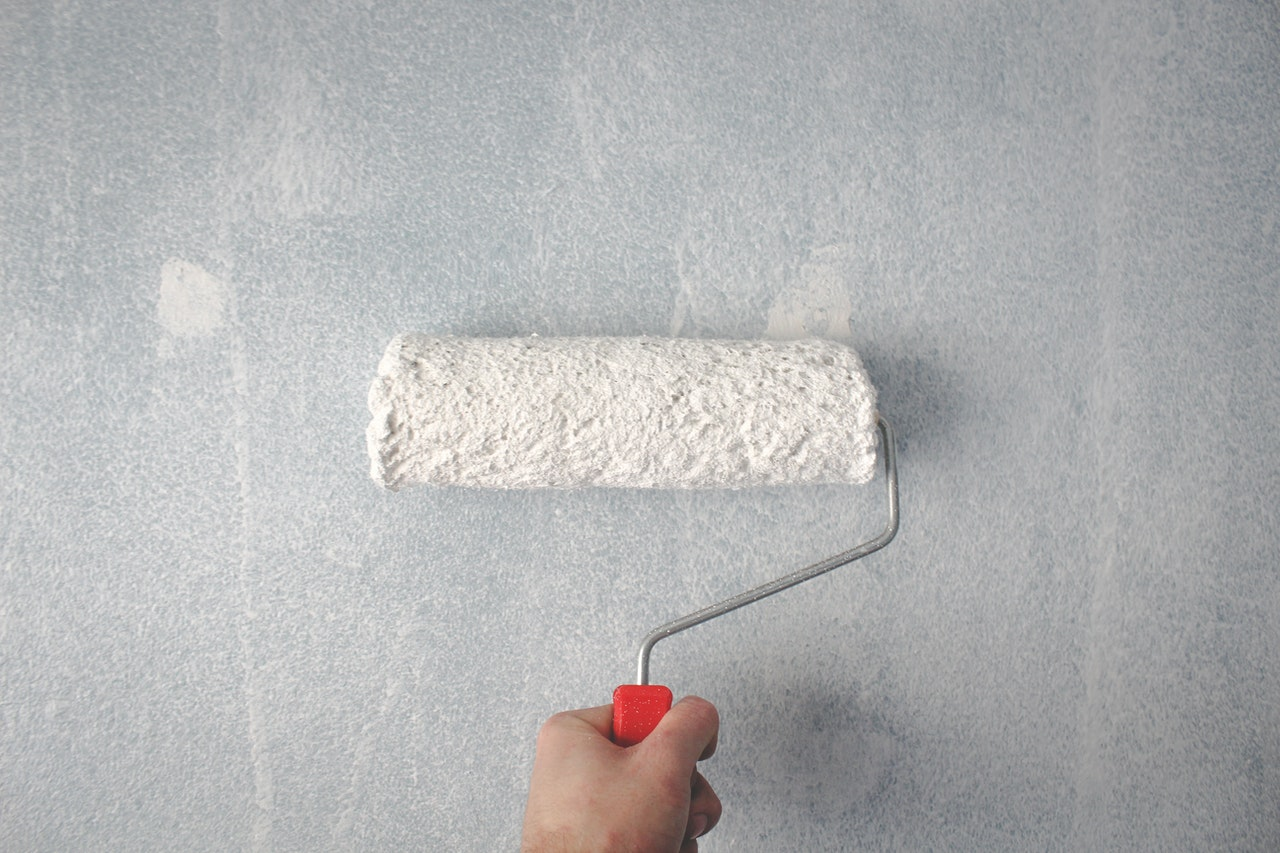 person painting a wall