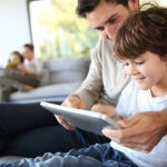 father and son playing games on the tablet