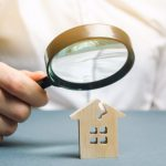person using a magnifying glass on wood house